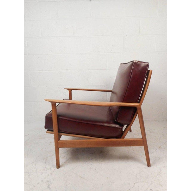 This gorgeous vintage modern lounge chair features a sculpted teak frame with thick padded vinyl cushions. Quality...