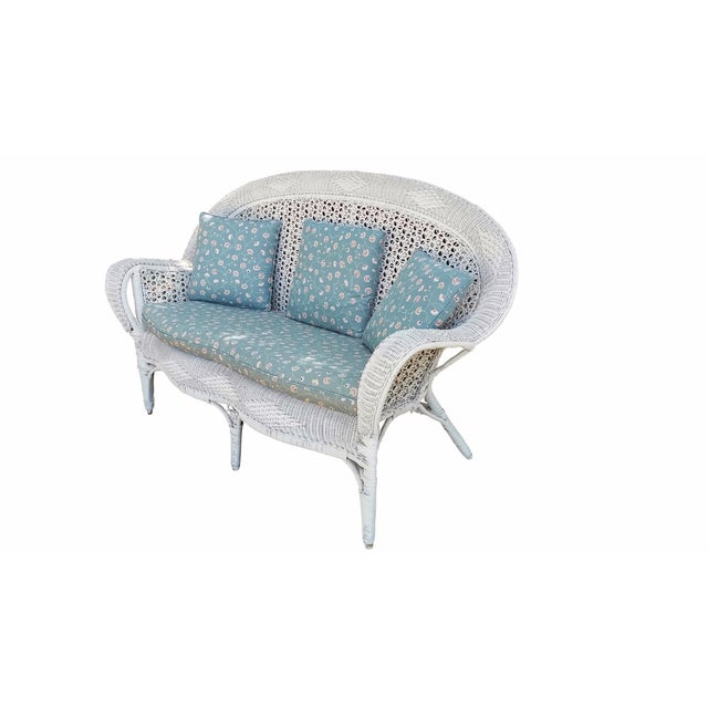 A Heywood Wakefield style white wicker settee. A highly decorative wicker lattice covers a bentwood bamboo frame. The...
