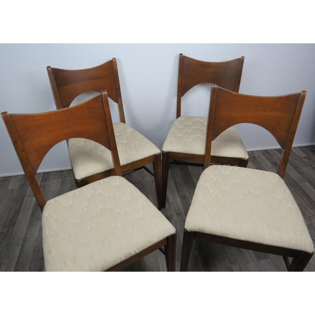 Mid-century modern walnut bow-tie chairs manufactured by Lenoir. Original white blended cotton felt fabric. Solid frame...