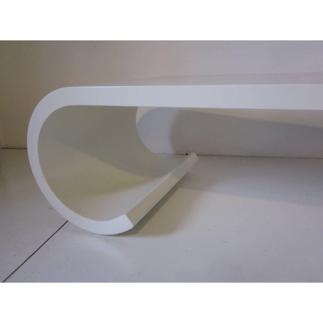 A wood bone white satin scroll coffee table in the manner of Karl Springer a sculptural and appealing form with clean and...