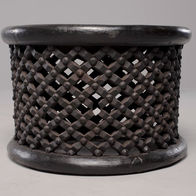 Circa 1980s round table or stool from Bamileke people in Cameroon is made of dark stained carved wood with an open work...