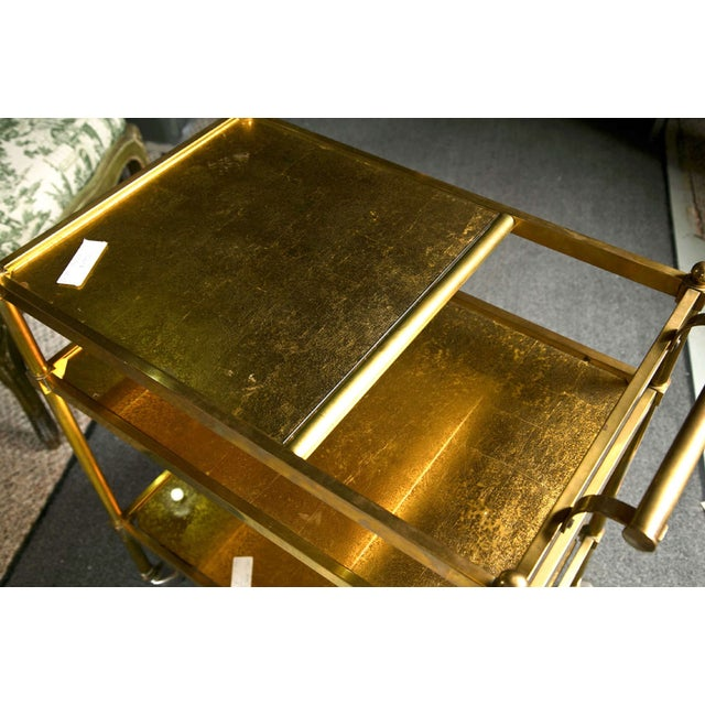 French Art Deco style gilt-brass tea cart. Circa 1960s. This piece has a total of three gilt-glass tops. Rolling on casters.