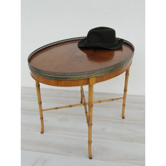This is a Baker Furniture Holland Salley Inc., small end table made with bamboo and a brass trim that has a heart cutout...