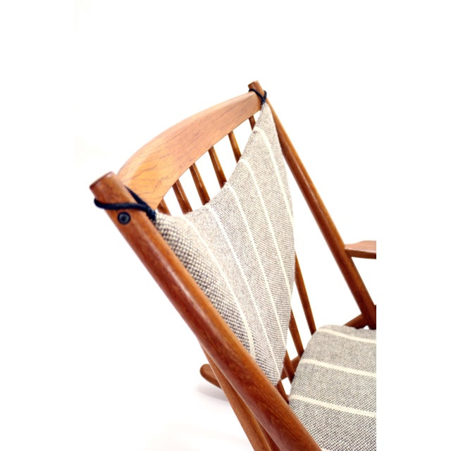 A Danish Mid-Century teak rocking chair by Frank Reenskaug for Bramin Møbler with original cushions and upholstery. This...