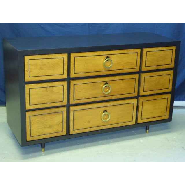 Smart nine-drawer chest of drawers featuring brass ring pulls and tapered legs with brass sabots. Its brass pulls and...