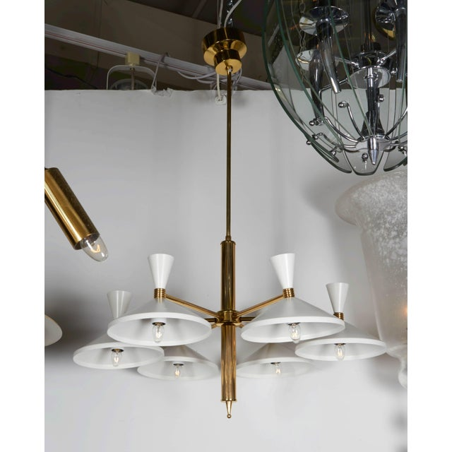 A 1950s modern design brass and white enamel metal six-light chandelier. Each brass arm holds a wide down facing shade...