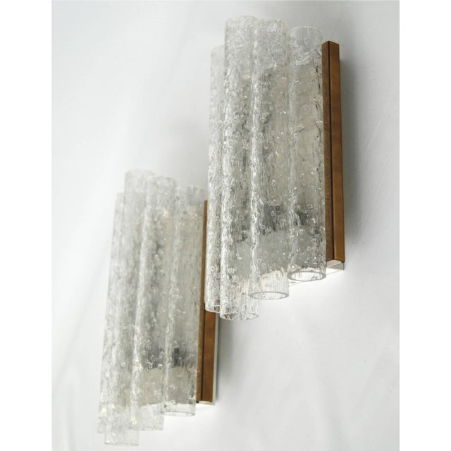 A pair of wall lights by Doria, Germany, circa 1960. Textured glass tubes with brass trim. Existing wiring, we do not...
