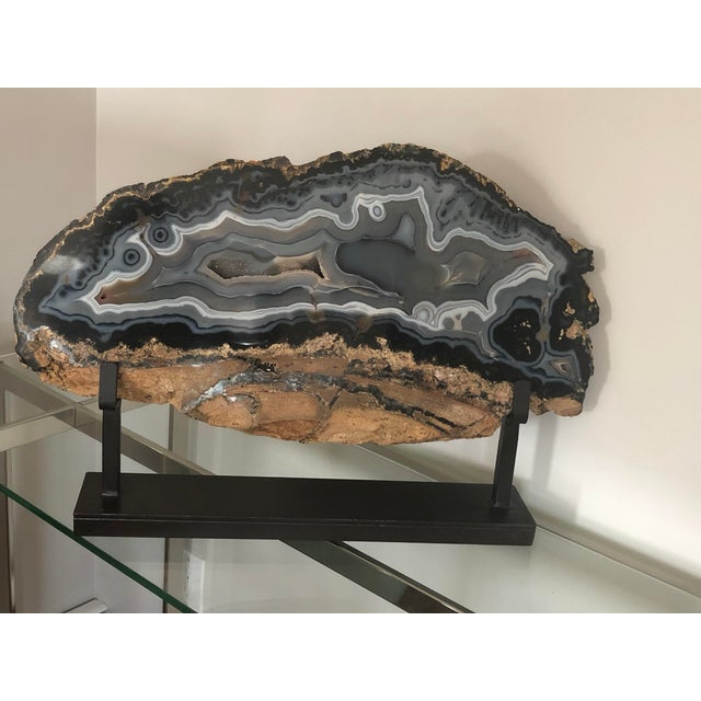 Organic polished agate with blues, grays and creams. Sits on an iron stand. The stunning contrast in texture and form...