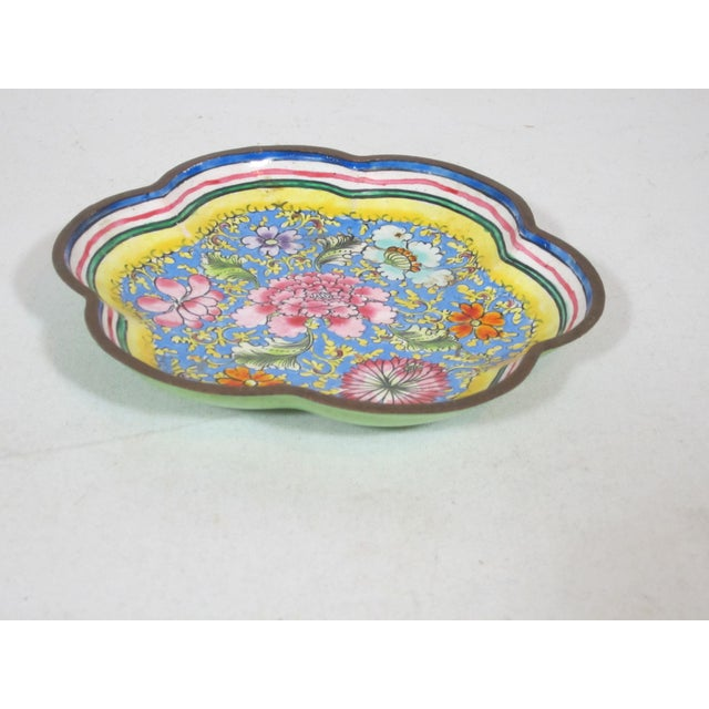 Scalloped shaped hand painted enameled tray on brass. The tray is decorated with a bright floral design on a blue back...