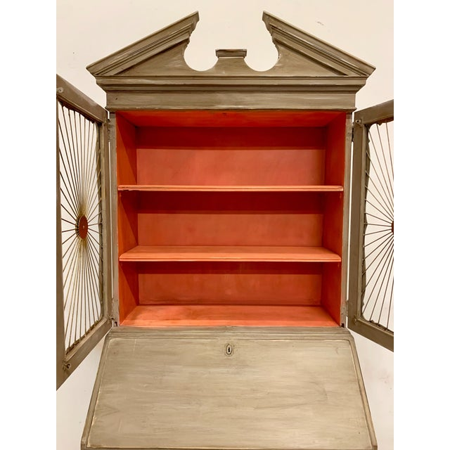 This is a hand painted secretary by John Widdicomb with a sunburst wire front. The finish is a glazed French gray and...