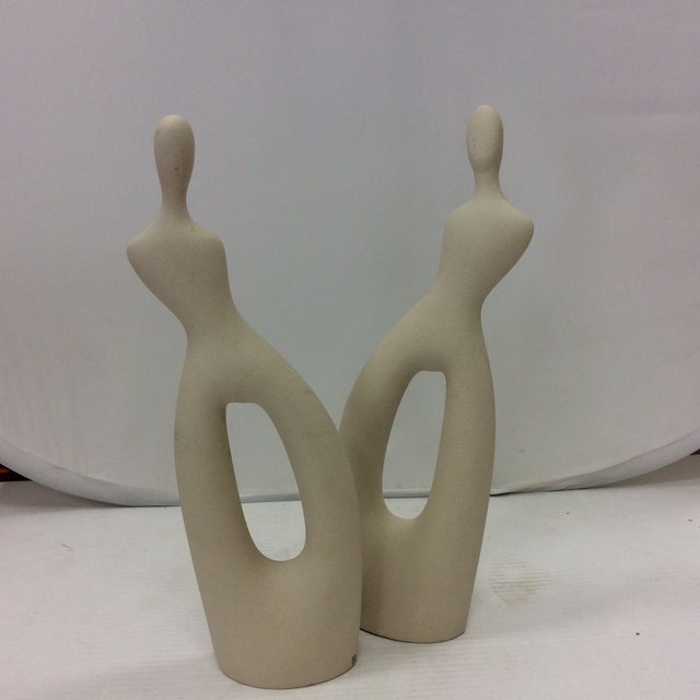 A lovey abstract pair of tall figures by Angelo Spagnolo for Linea Setta. Hand formed porcelain with a slip glaze sand...