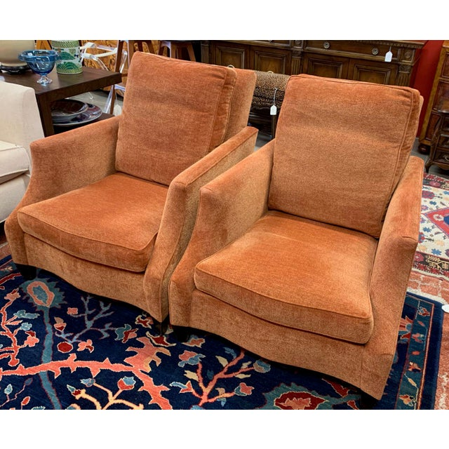 Pair of deep, high back club chairs made by Donghia. The design has a serpentine front, scooped arms and a steeply racked...