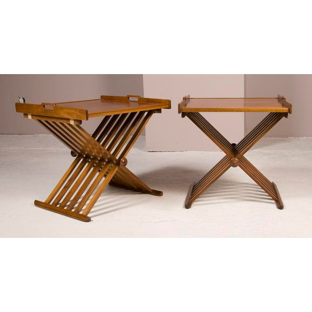 A pair of walnut folding campaign style tables with removable trays. By Stewart MacDougall for Drexel. American, circa 1960.