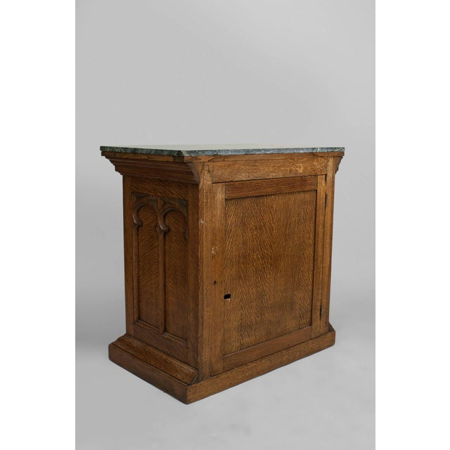 English Gothic Revival style 19th-20th century oak carved commode with arch design on two front doors and sides with a...