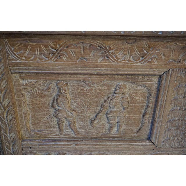 18th century Flemish blanket trunk or coffer featuring three panels of carved figural scenes surmounting a scalloped apron...