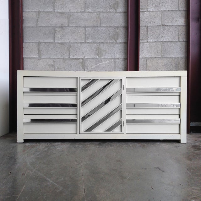 1970s glam white lacquered dresser with chrome trim pulls. Features three drawers on either side and a center cabinet....