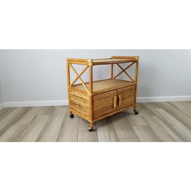 This artisan-crafted Rattan bar cart is designed of handwoven rattan storage on the bottom with cane tops.
