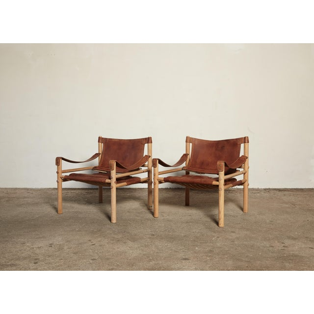 A lovely original pair of Arne Norell safari sirocco chair wtih wood frames and patinated brown leather seats. In lovely...