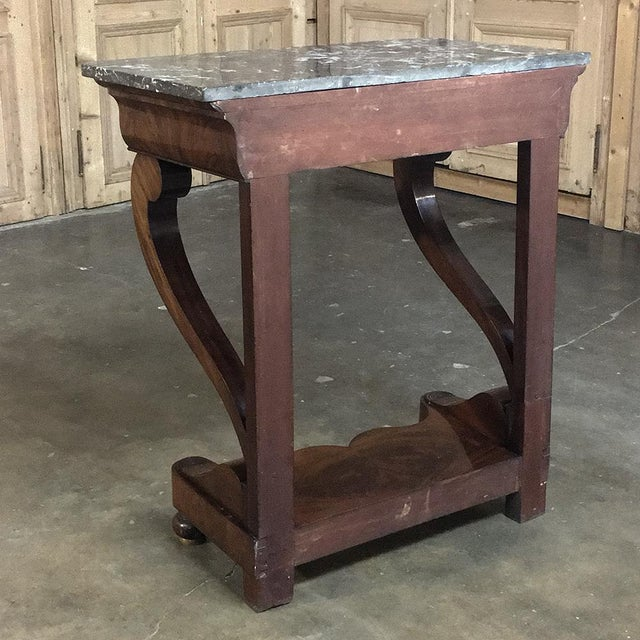 Representing the essence of the style, this 19th Century French Louis Philippe Mahogany Marble Top Console features...