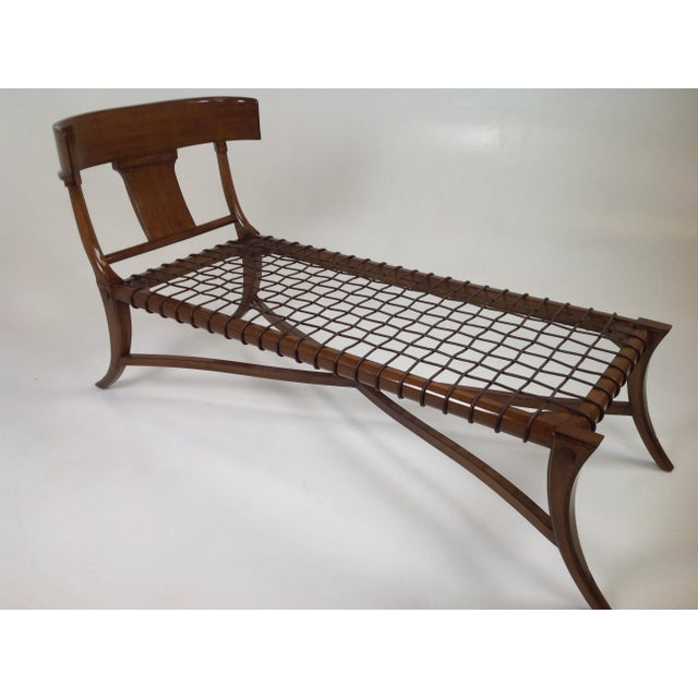 Sophisticated modern chaise lounge in the manner of Robsjohn Gibbings Klismos. The chaise has a walnut finish, with...