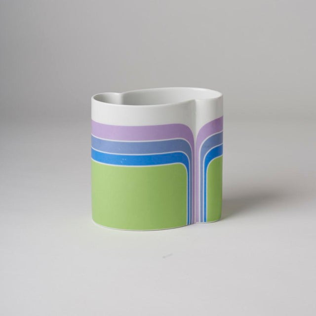 Wonderful colorful Op Art Vase, swirled lines of purple, and blues against green background.