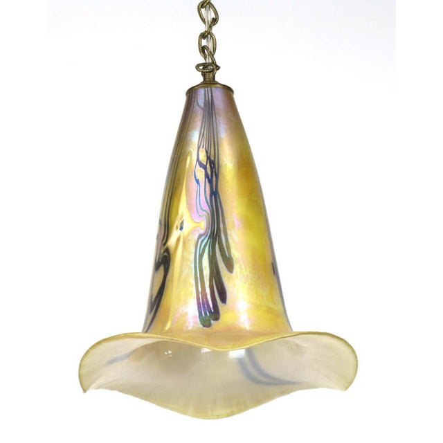 Delicate and colorful iridescent art glass pendant light. Luminous colors of ochre, lavender, violet and turquoise seem to...