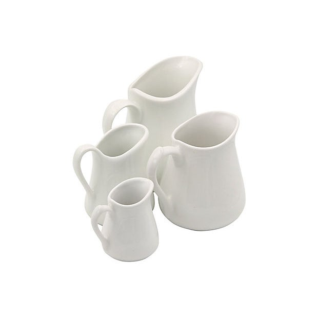 "Set of four graduating French porcelain pitchers. Dimensions: Largest to smallest, 6.5""L x 4.75""W x 6""H to 3.5""L x 2.5""W x..."