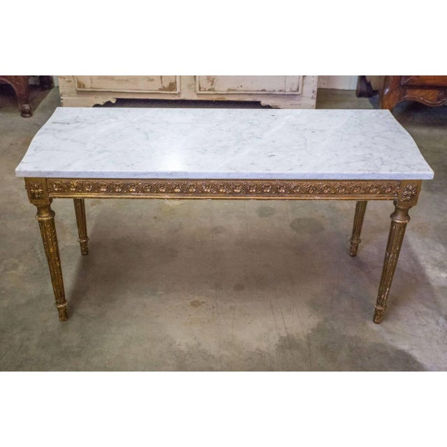 French gilded coffee table with Carrara marble top in original unrestored condition. Classic Louis XVI style with rosettes...