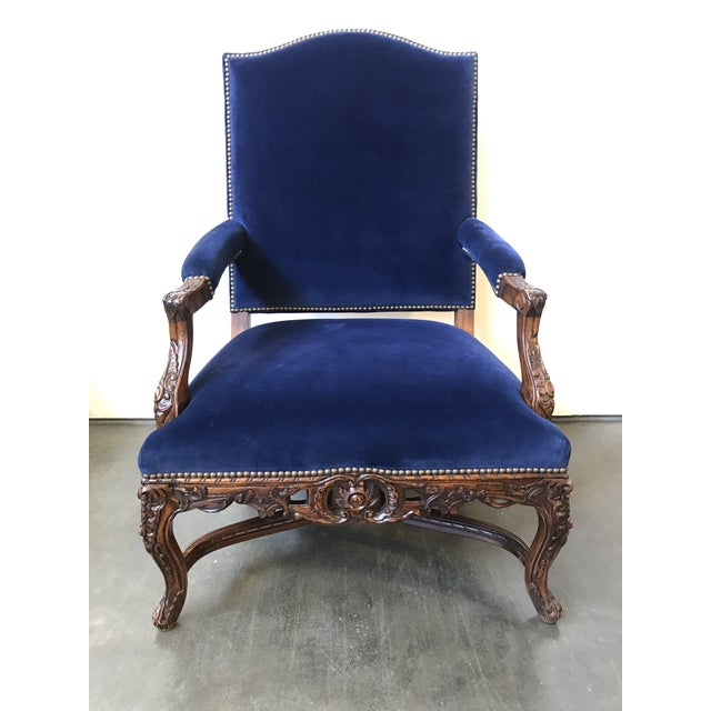 Beautifully carved fruitwood finish frame with seat, back and arms upholstered in a blue velvet. Nailhead trim around...