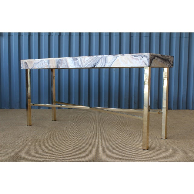 Onyx top console table on a custom brass-plated base.
