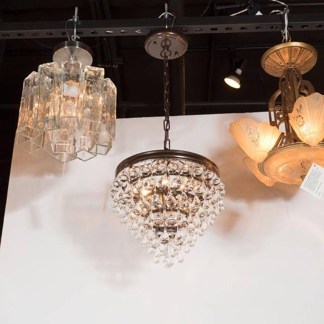 A Hollywood Regency crystal teardrop and ball chandelier with bronze fittings. A bronze canopy and chain support a frame...