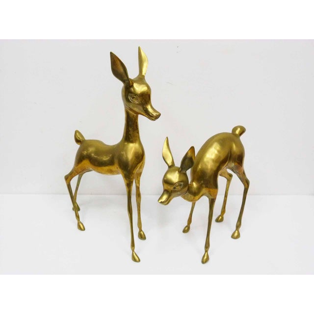 A large, vintage pair of brass deer floor sculptures featuring a standing doe and a fawn feeding. No makers mark. Large...