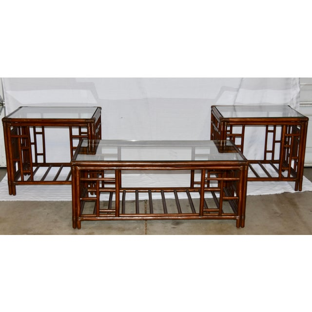 McGuire Style Bamboo Rattan Glass Top Table Set Sleek and modern bamboo and rattan coffee and end tables that features...