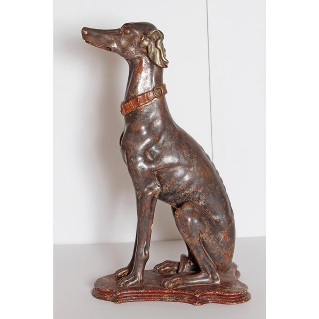 A fine example of a tall Italian greyhound sculpture from the late 19th century. The greyhound is sitting quietly on a...
