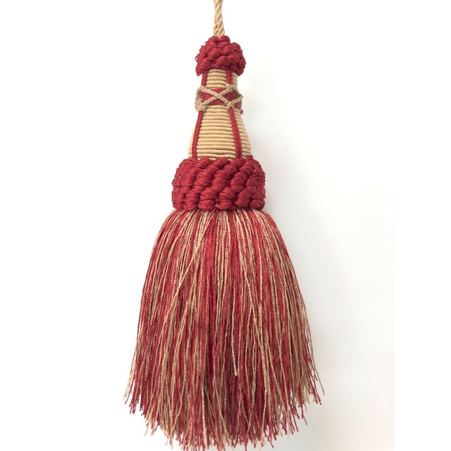 Handmade red & gold colored key tassel with looped ruche, twisted cord and full skirt. This tassel is a true ruby red and...