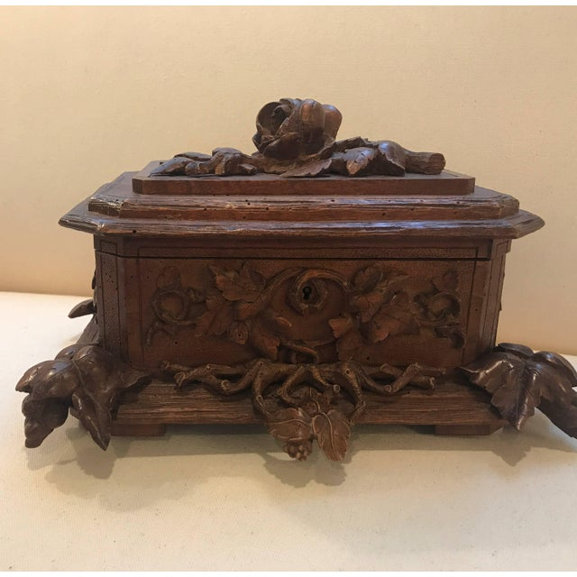 Expertly hand-carved Swiss black forest hand-carved table box. The hinged lid with floral and vine decoration over a...