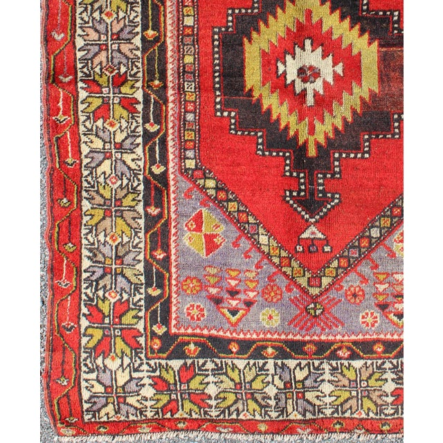 This antique Oushak rug features an intricate and complex design paired with a unique color combination. A central...
