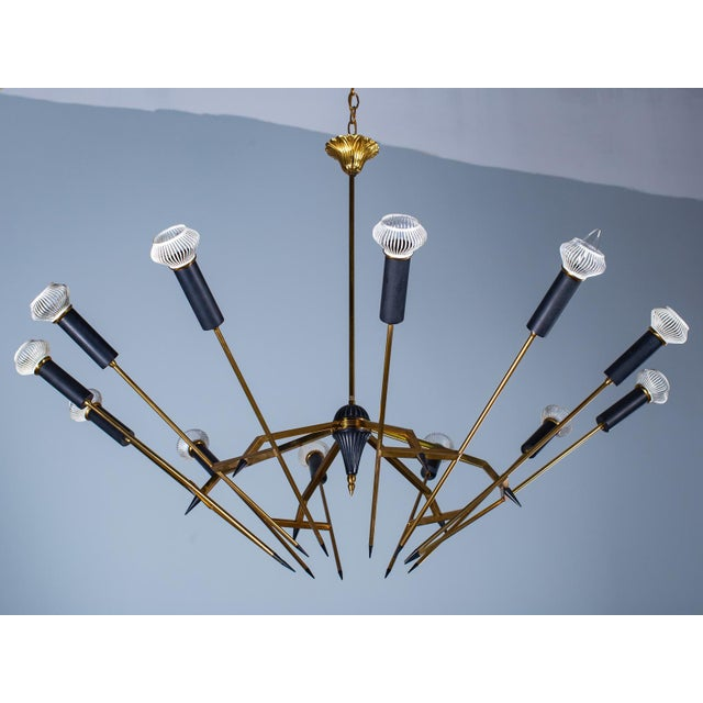 This mid century brass and black twelve light chandelier is reminiscent of the designs created by the Italian lighting...