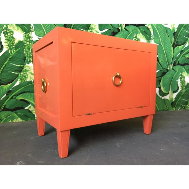 Pair of nightstands in an orange-salmon high gloss lacquer. Solid brass ring pull hardware. Drop door reveals large...