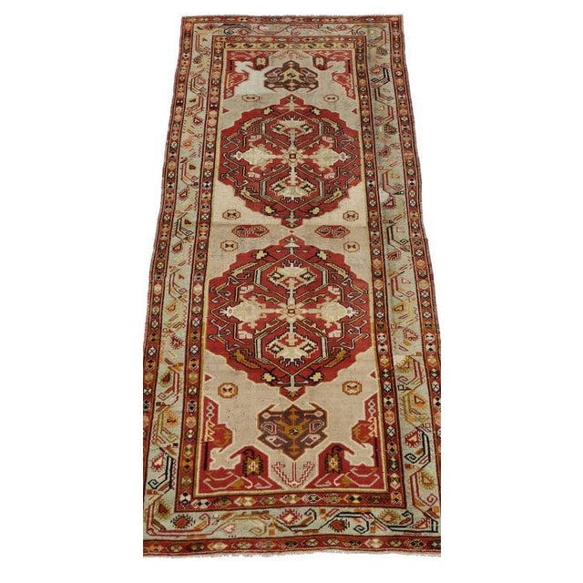 Hand-knotted wool vintage Turkish Oushak runner featuring two large geometric medallions and tribal motifs in an open...
