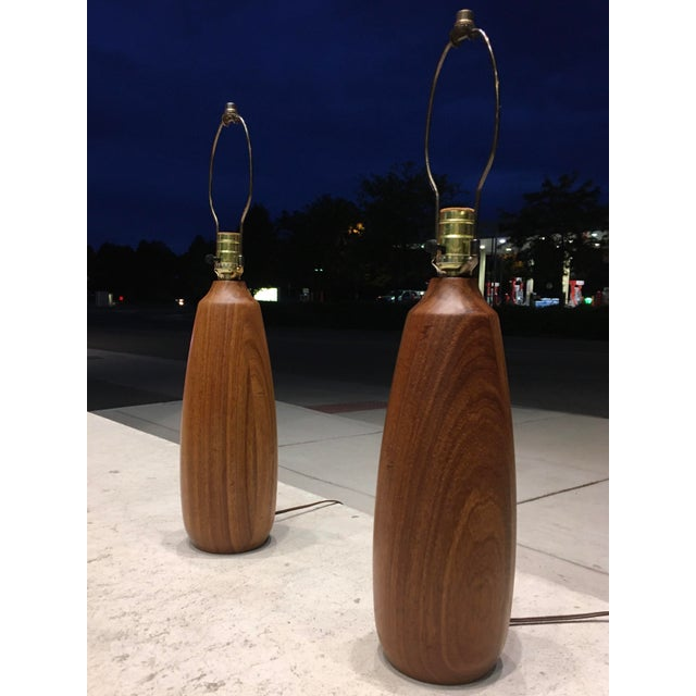 Pair of handsome turned teak table lamps by Gordon Martz for Marshall Studios, circa 1960s. Piece dimensions: Lamps stand...