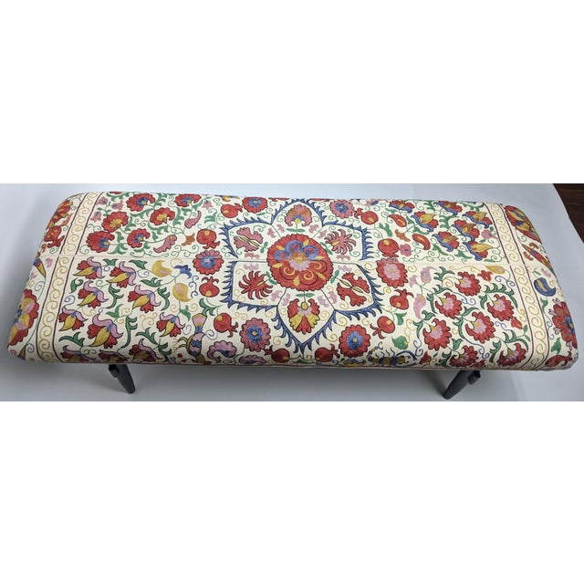 Spectacular bench upholstered with antique suzani. This 19th century Suzani is made of hand embroidered silk dyed...