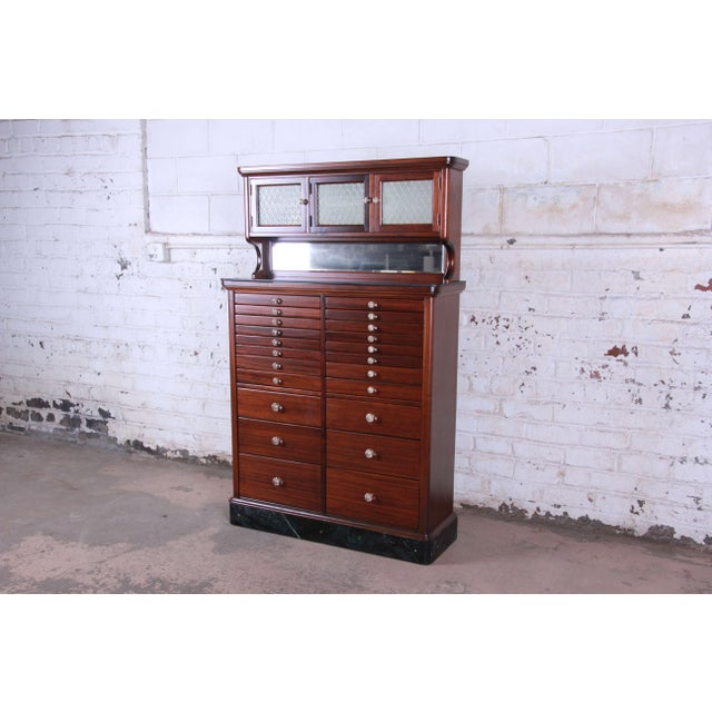Offering a truly unique and extraordinary antique mahogany marble base dental cabinet manufactured in 1929. The piece...