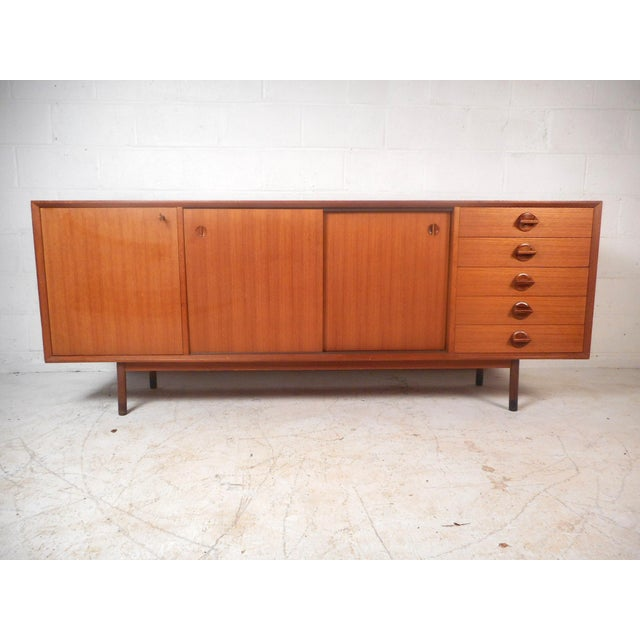 A stunning Mid-Century Modern sideboard with sculpted rosewood pulls, a finished back, and a rich vintage teak finish....