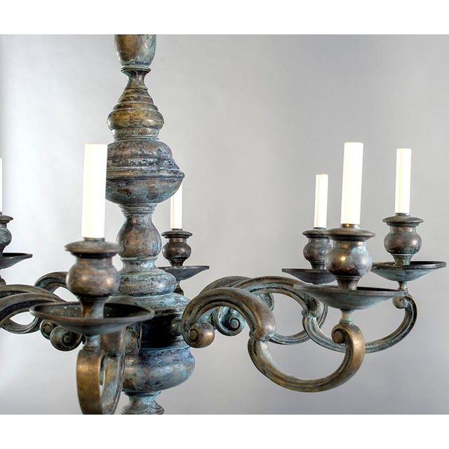 Circa 1930s chandelier found in Belgium with patinated brass frame and eight candle style lights. Chandelier has been...