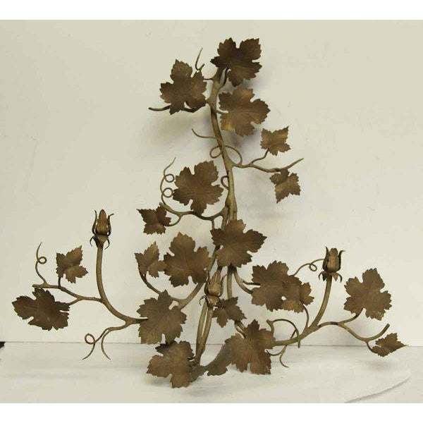 Bronze finished metal wall decor with leafy detail and three arms. Priced as a pair.