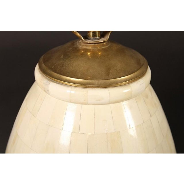 This is a pair of tessellated bone table lamps. Each lamp is of ovoid form, and is raised on a circular brass base. These...