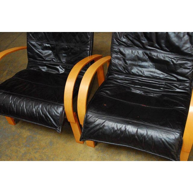 Stylish pair of Mid-Century Danish black leather armchairs featuring a bentwood frame with curved arms and metal supports....