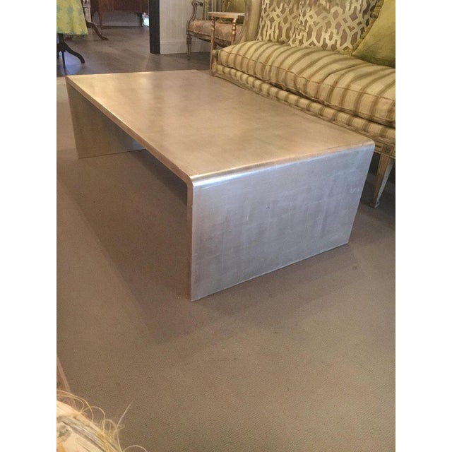 Very chic waterfall coffee table with silver leaf finish in the style of Jean Michel Frank. Great size and proportions.