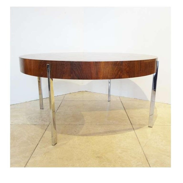 Round modernist cocktail table featuring a thick wood top with a deep skirt in highly figured Walnut with four thin...